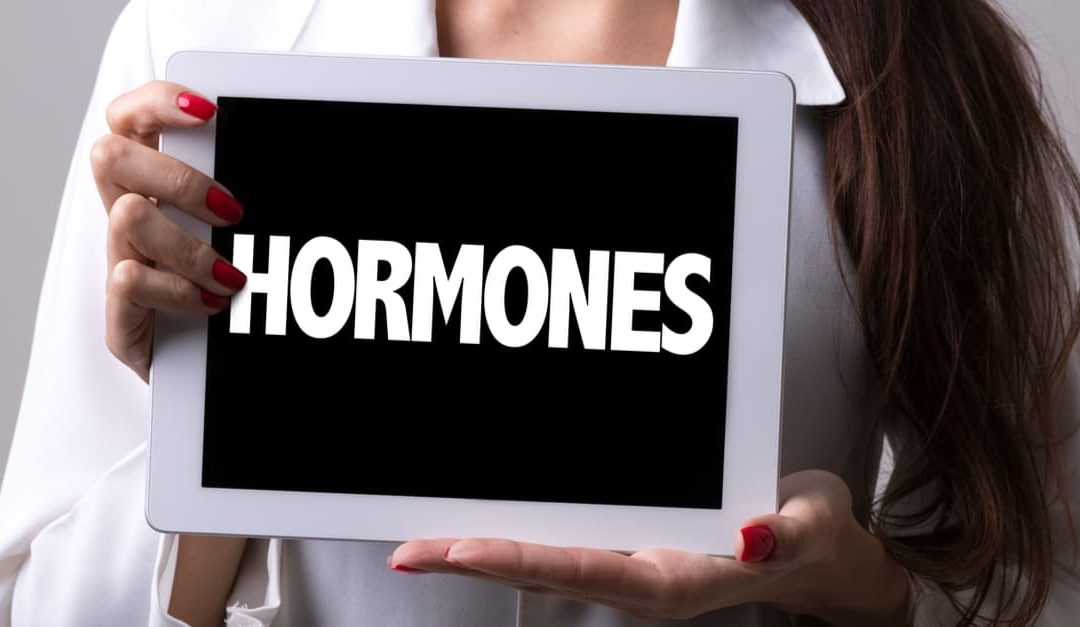 woman holding a hormones sign to teach what are hormones?