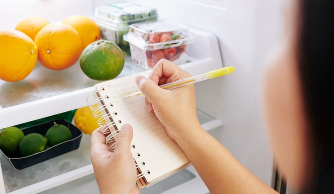 woman writing a vitamin list from the food in her refrigerator