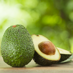 whole avocado and avocado pieces on a wooden table with a nature background