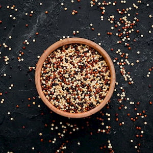 bowl of red, white and brown quinoa on a black background