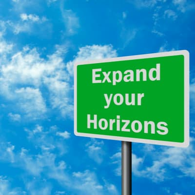 expand your horizons sign with a blue sky background