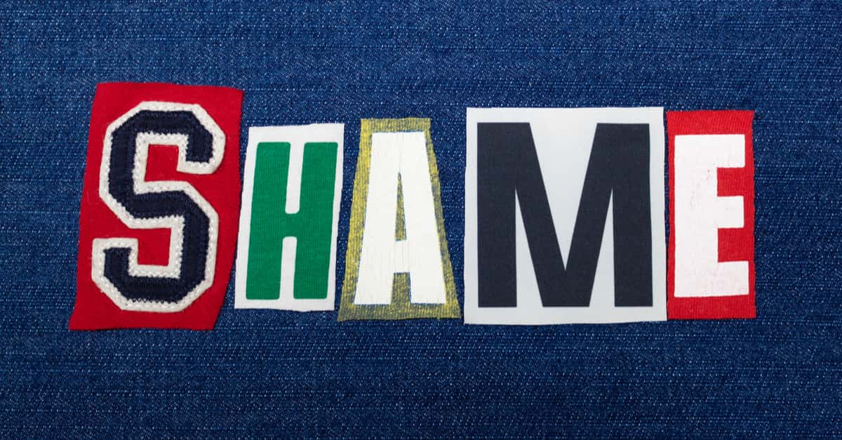 SHAME text word collage, colorful fabric on blue denim, guilt and blame concept