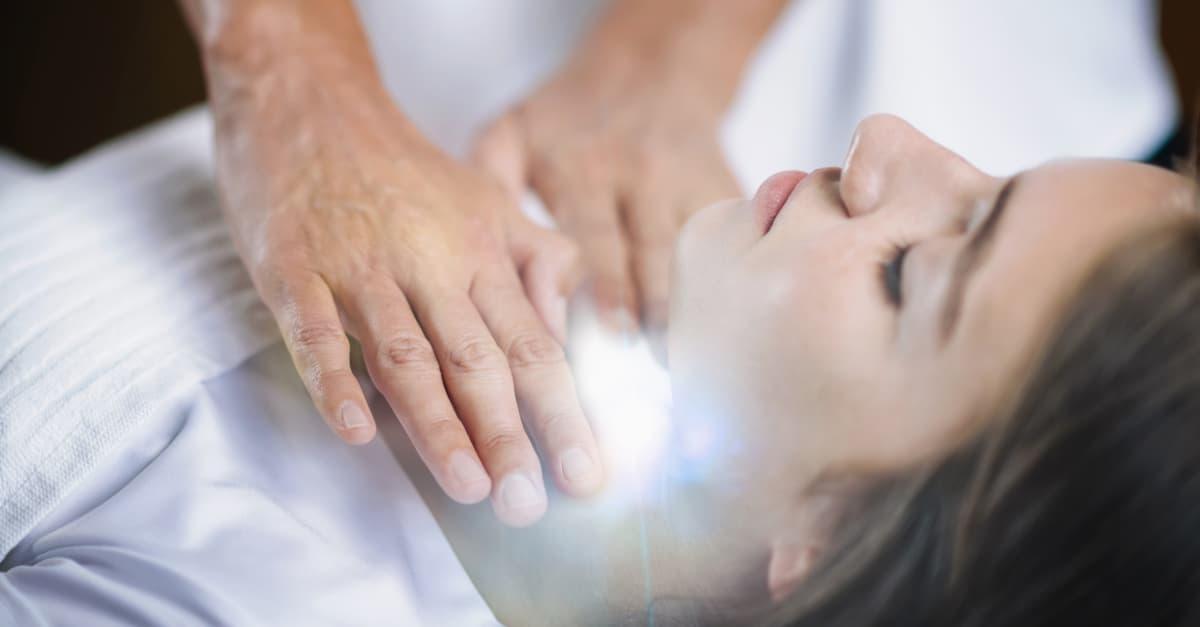 Reiki practitioner standing and healing throat chakra