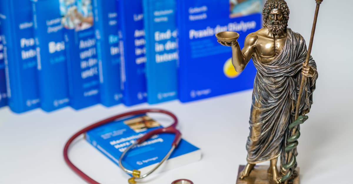 Bronze statue of Hippocrates surrounded by medical books