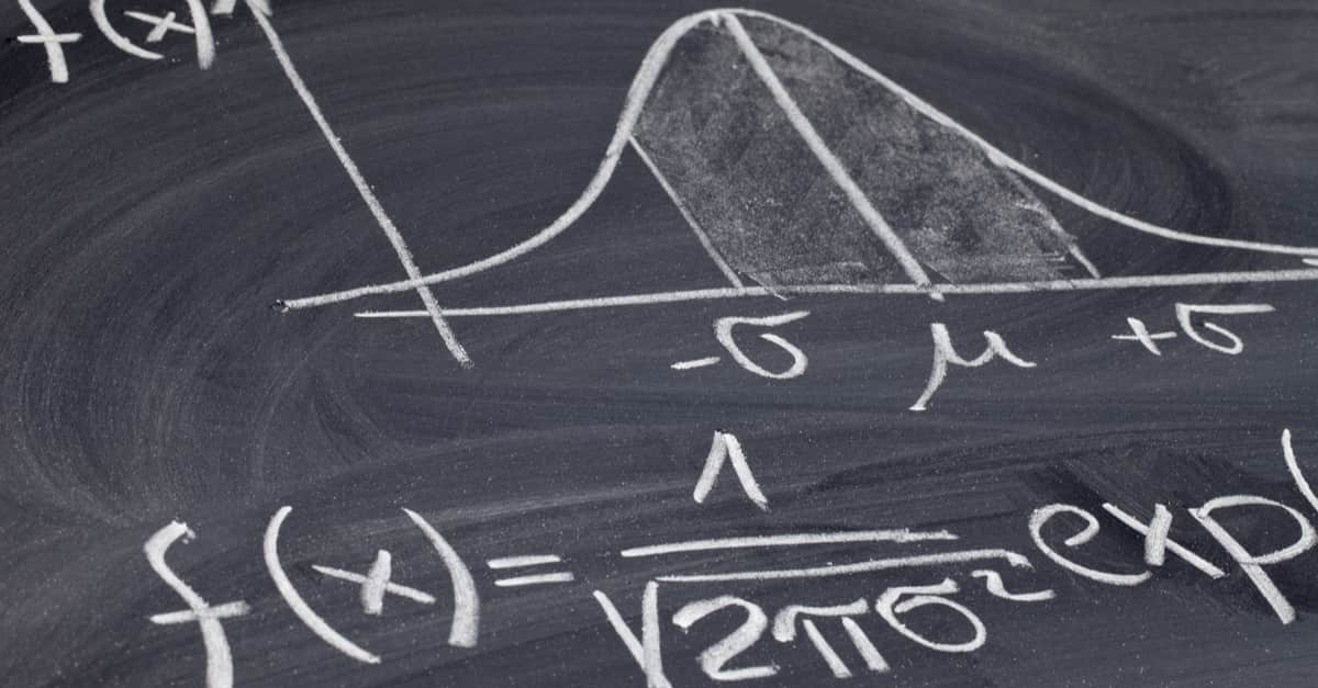 Gaussian, bell or normal distribution curve with equation sketched with white chalk on a blackboard