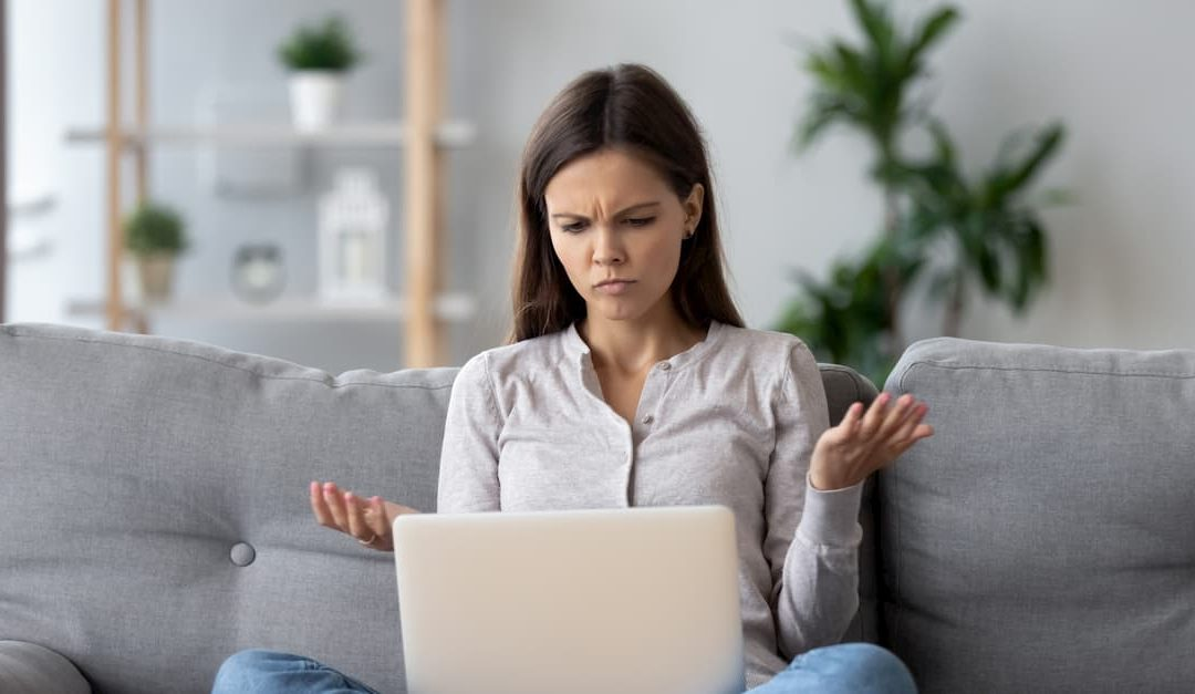 Woman confused at her laptop wondering if scalar light is a scam