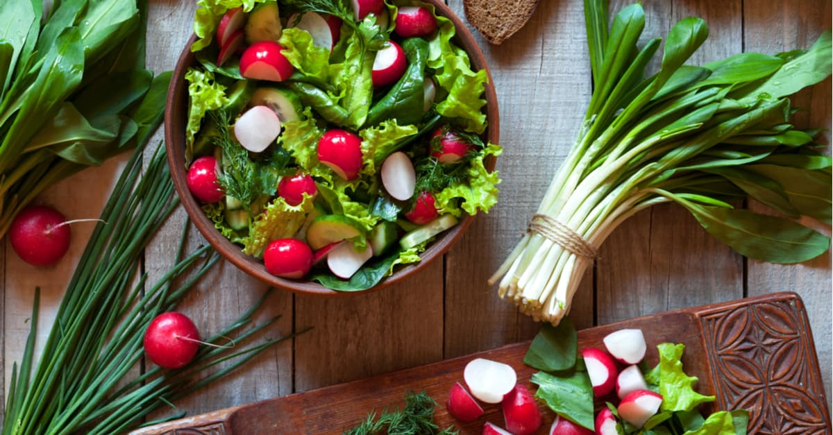 Fresh salad with cucumber, radishes, spinach, ramson, garlic in ceramic bowl on old wooden table