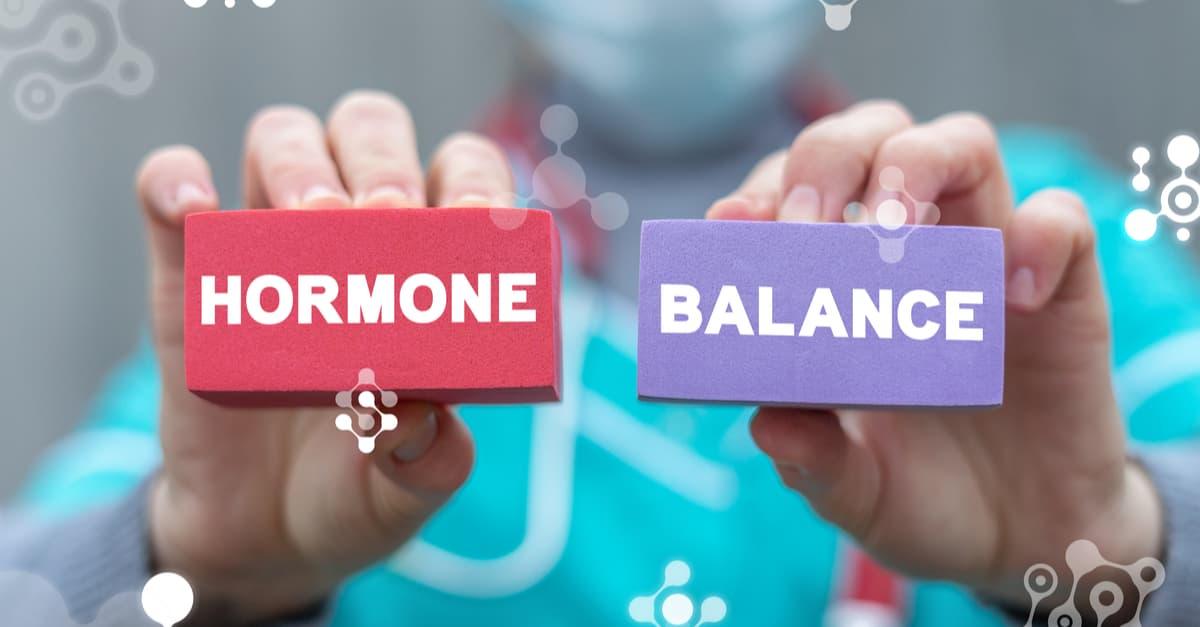 Nurse holding up two colored blocks stating 'hormone balance'