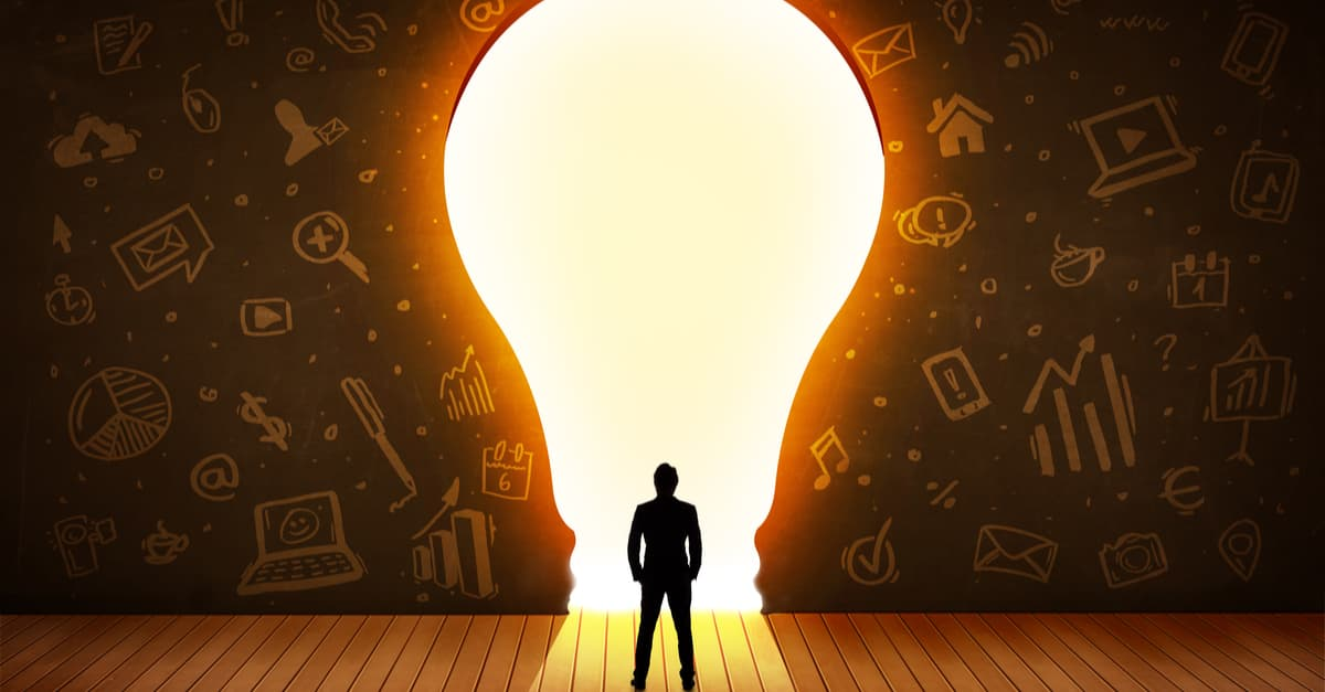 Man standing in front of a large light bulb, being illuminated with ideas.